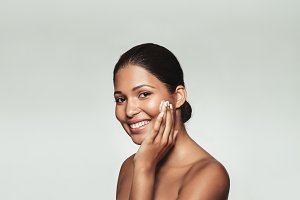 Smiling woman applying moisturizer