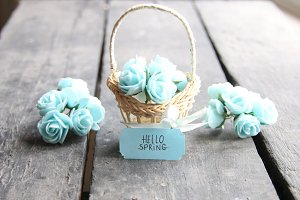 hello spring tag and flowers in a small basket on a vintage background