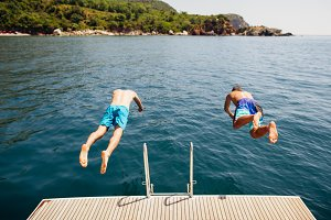 men jumping into sea water