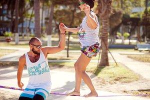 couple on slackline balancing