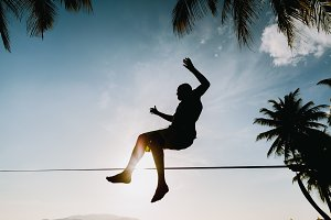 man jumping and balancing slackline