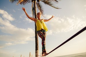 teenage girl slacklining on beach