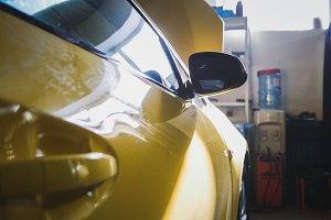 Door of yellow car in garage auto service - for repairing