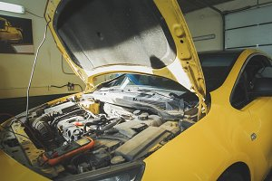 Yellow car in garage auto service - open hood - engine repairing