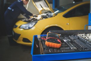 Defocused view - mechanic repairs a car - unscrews detail of automobile - garage service