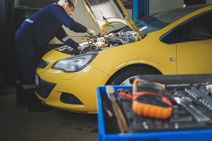 Mechanic repairs a car - unscrews detail of automobile - garage service