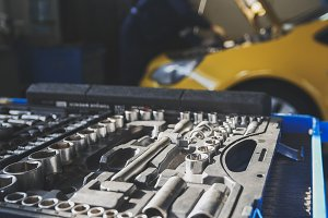 Mechanic repairs yellow car in professional auto service, de-focused