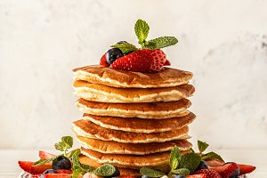 Homemade pancakes with berries and fruit on a white background.