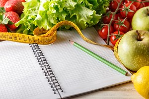 Fresh organic vegetables and fruits, open blank notebook and pen