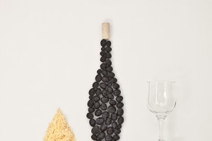 Bottle of wine, glass, cheese.