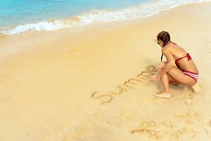 Young beautiful woman writing SUMMER on the beach sand near sea. Pretty young girl in swim wear enjoy summer vacation on beach and draw on sand. Attractive white female at seaside on tropical island