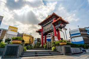 Cityscape photography of Chinatown in Bangkok with colorful Gateway Arch made with traditional ornament of red and golden colors. Odeon Circle landmark of Chinatown in Thailand