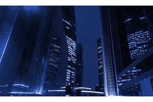 Tall office buildings by night. Concept in blue tone