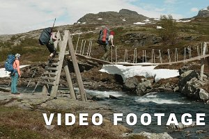Backpackers go on the bridge through the river in Norway