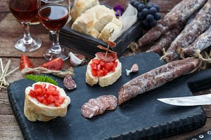 sliced bread, tomato and sausage for bruschettas on wooden cutting board