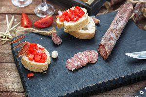 Slices of salami, baguette and tomato on the wooden board
