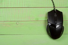 black computer mouse on a green wooden background with copy space for your text. Top view