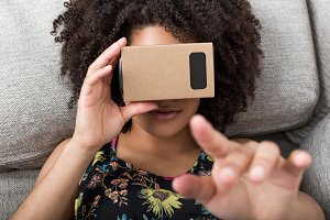 Young woman using cardboard VR