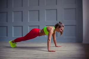 Beautiful fitness woman is doing push-ups in the gym,
