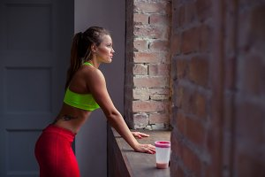 Good-looking fitness girl with tattoo in green top is standing in the gym nearby big windows, looking there and thinking. She is exhausted after training