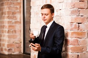 Young handsome businessman in black suit is drinking coffee and surfing in the phone near brick wall