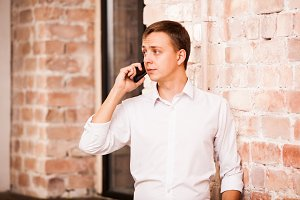 Handsome businessman in white shirt is speaking on the phone near the brick wall