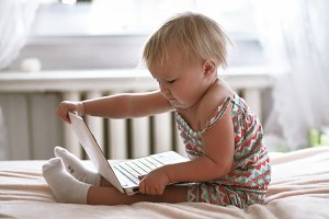 Toddler kid with laptop at home