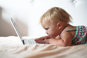 Blond toddler and gadget laptop