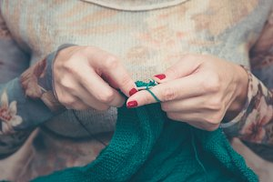 manicured woman hands knitting green plaid