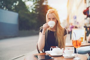 Lady drinking tea in street bar