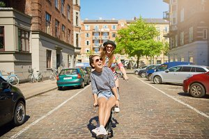 Teen in hat riding with girl on bike on street