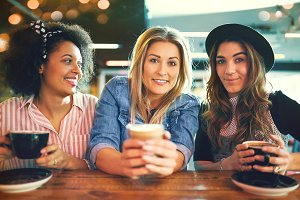 Three trendy young women enjoying coffee