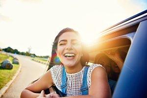 Pretty woman in speeding car smiles at camera