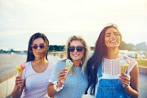 Three joyful young girlfriends on a promenade