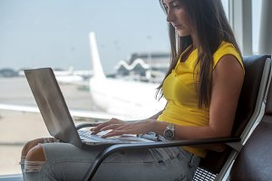 Young woman holding a laptop on lap typing keyboard indoors in airport