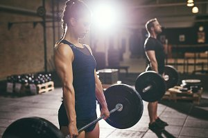 Man and woman doing deadlift with barbells