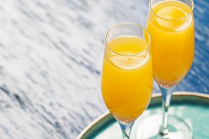Two glasses with mimosa cocktail (cava plus orange juice)