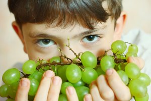 preteen handsome boy with green grapes close up portrait