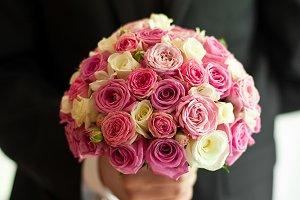 Groom holds pink wedding bouquet