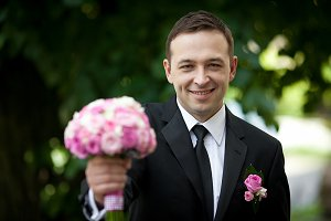 Smiling groom holds wedding bouquet