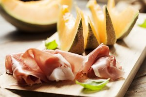 Slices of cantaloupe melon and prosciutto ham, shallow DOF