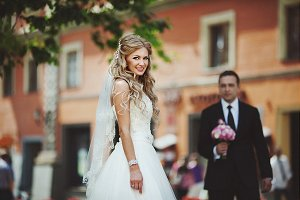 Blonde bride poses on the street