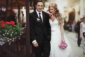 Pretty blonde bride leans on groom
