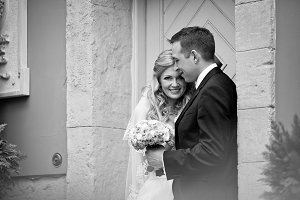 Newlyweds standing at an old door