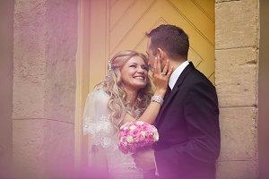 Happy bride hodls groom's face