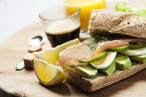 Rye bread sandwich with avocado, eggs, cucumber and smoked salmon