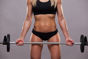 Closeup athletic torso of woman in sporty cloths. She is holding a barbell on grey background with copyspace
