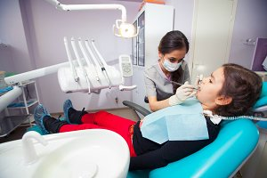 pretty little girl opening his mouth wide during treating her teeth by the dentist