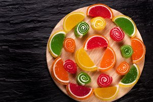 Fruit jellies. Jelly candies citrus in form lobules on a dark background. Top view