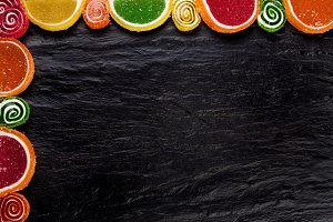 Frame from fruit jellies on a dark background. Top view with copy space